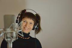 Adolescente nelle cuffie vicino ad un microfono in a Fotografie Stock