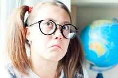 Adolescente nerdy elegante en lentes negras que se pregunta seriamente Fotos de archivo