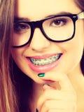 Adolescente nerdy feliz con las lentes que llevan del apoyo Imagen de archivo libre de regalías