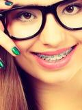 Adolescente nerdy feliz con las lentes que llevan del apoyo Foto de archivo libre de regalías