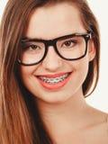 Adolescente nerdy feliz en las lentes que muestran apoyos Fotos de archivo
