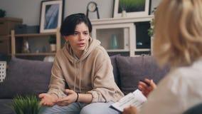 Adolescente nervoso che comunica con lo psicanalista femminile durante la sessione video d archivio