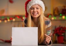 Adolescente no chapéu de Santa que mostra a folha do papel vazio Fotografia de Stock