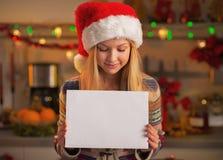 Adolescente no chapéu de Santa que mostra a folha do papel vazio na cozinha Fotografia de Stock