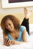 Adolescente no quarto com telefone móvel foto de stock
