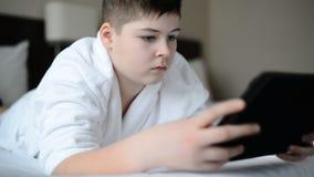 Adolescente no roupão branco na cama e no jogo na tabuleta vídeos de arquivo