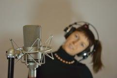 Adolescente nos fones de ouvido perto de um microfone na Fotos de Stock Royalty Free