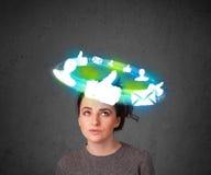 Adolescente novo com ícones sociais da nuvem em torno de sua cabeça Foto de Stock Royalty Free
