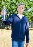 Adolescente novo com a garrafa da água no parque foto de stock royalty free