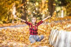 Adolescente novo feliz que paga no parque do outono foto de stock royalty free