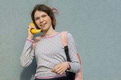 Adolescente novo que fala no telefone, realizando na banana abstrata do receptor de telefone das mãos Copie o espaço, fundo cinze fotografia de stock