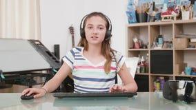 Adolescente novo que joga um jogo em seu computador