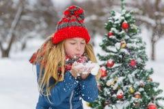 Adolescente o muchacha lindo que adorna el árbol de navidad al aire libre Imagen de archivo libre de regalías