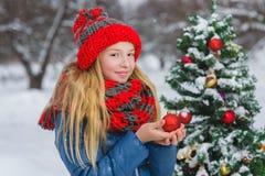 Adolescente o muchacha lindo que adorna el árbol de navidad al aire libre Imágenes de archivo libres de regalías