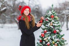 Adolescente o muchacha lindo que adorna el árbol de navidad al aire libre Fotos de archivo