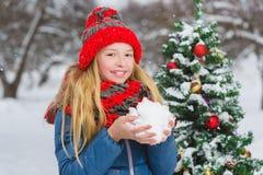 Adolescente o muchacha lindo que adorna el árbol de navidad al aire libre Fotografía de archivo