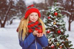 Adolescente o muchacha lindo que adorna el árbol de navidad al aire libre Foto de archivo