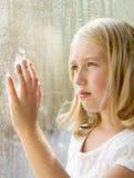 Adolescente o niño que mira hacia fuera una ventana Foto de archivo libre de regalías