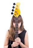Adolescente ocultado detrás de la guitarra baja Fotos de archivo libres de regalías