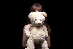 Adolescente ocultado detrás del oso de peluche Foto de archivo