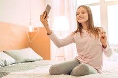 Adolescente optimista que toma el selfie en cama Imágenes de archivo libres de regalías