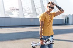 Adolescente ordenado que mantiene hoverboard brazo Fotografía de archivo