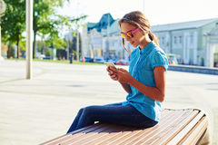 adolescente Oscuro-cabelludo que se sienta en banco de madera en la ciudad y Imagen de archivo