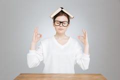 Adolescente pacifico che si siede con il libro sulla testa e sul meditare Immagine Stock