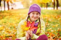 Adolescente para pasar tiempo con las hojas de otoño Muchacha en las hojas de otoño en el parque en el aire fresco Imagenes de archivo