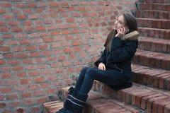 Adolescente parlant sur le smartphone dehors image stock