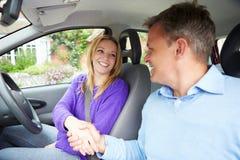 Adolescente passant l'examen de conduite avec l'examinateur Photographie stock libre de droits