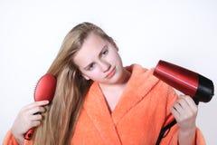 Adolescente peinándose el pelo usando un hairdryer para secarse Foto de archivo