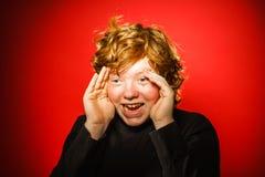 Adolescente pelirrojo expresivo que muestra emociones en estudio Fotos de archivo