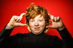 Adolescente pelirrojo expresivo que muestra emociones en estudio Imagen de archivo libre de regalías