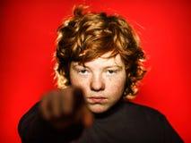 Adolescente pelirrojo expresivo que muestra emociones en estudio Foto de archivo