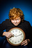 Adolescente pelirrojo expresivo que muestra tiempo en el reloj grande Imagenes de archivo