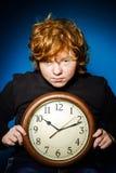 Adolescente pelirrojo expresivo que muestra tiempo en el reloj grande Imágenes de archivo libres de regalías