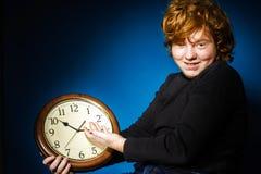 Adolescente pelirrojo expresivo que muestra tiempo en el reloj grande Foto de archivo libre de regalías