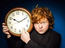 Adolescente pelirrojo expresivo que muestra tiempo en el reloj grande Fotos de archivo