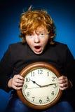 Adolescente pelirrojo expresivo que muestra tiempo en el reloj grande Fotografía de archivo libre de regalías