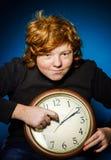 Adolescente pelirrojo expresivo que muestra tiempo en el reloj grande Foto de archivo