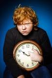 Adolescente pelirrojo expresivo que muestra tiempo en el reloj grande Imagen de archivo