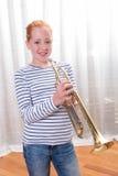 Adolescente pelirrojo que toca la trompeta Imagen de archivo libre de regalías