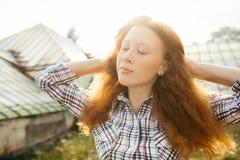 Adolescente pelirrojo sobre la luz del sol al aire libre que se relaja Imagen de archivo libre de regalías
