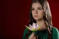 Adolescente pensativo. Adolescente bonito que sostiene una flor Fotos de archivo