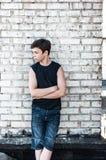 Adolescente pensativo cerca de una pared de ladrillo Imagenes de archivo