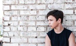 Adolescente pensativo cerca de una pared de ladrillo Imagen de archivo