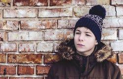Adolescente pensativo cerca de una pared de ladrillo Foto de archivo