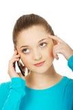 Adolescente pensativo con el teléfono móvil Fotografía de archivo libre de regalías