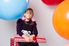Adolescente pensativo con los vidrios y los regalos Imagen de archivo libre de regalías